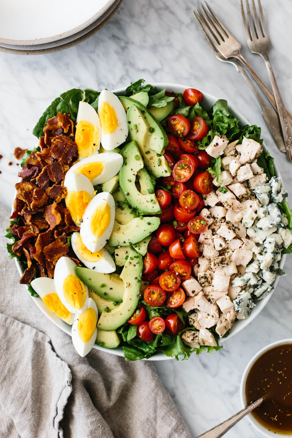 Cobb salad with bacon, hard boiled eggs, avocado, tomatoes, diced chicken and blue cheese in a bowl on a marble counter.
