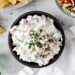 Creamy pico de gallo dip in a black bowl next to chips and salsa.