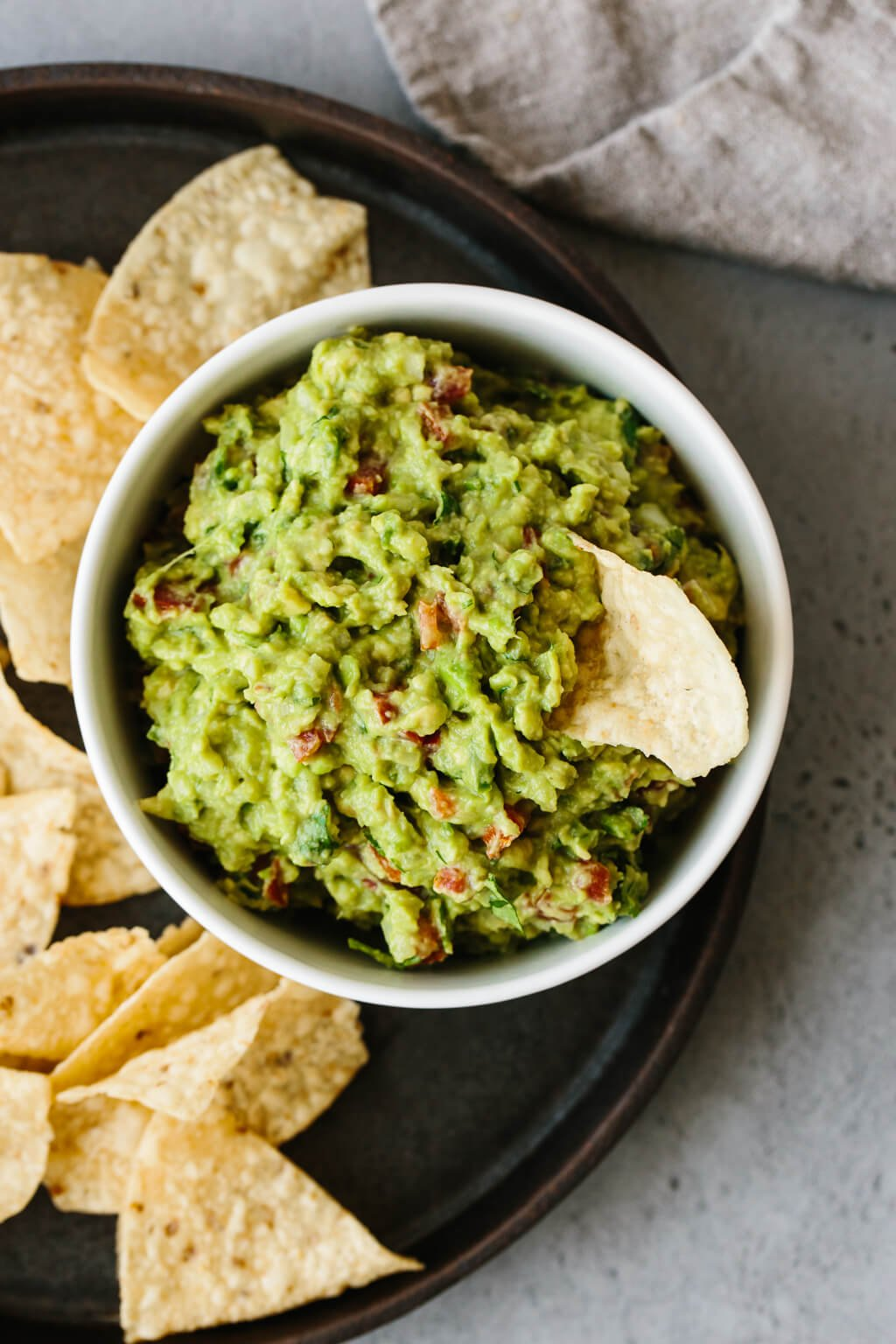Guacamole in a bowl surrounded by chips. One chip in the guacamole.