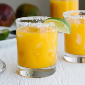 Mango margarita in a glass with a salted rim and lime wedge.