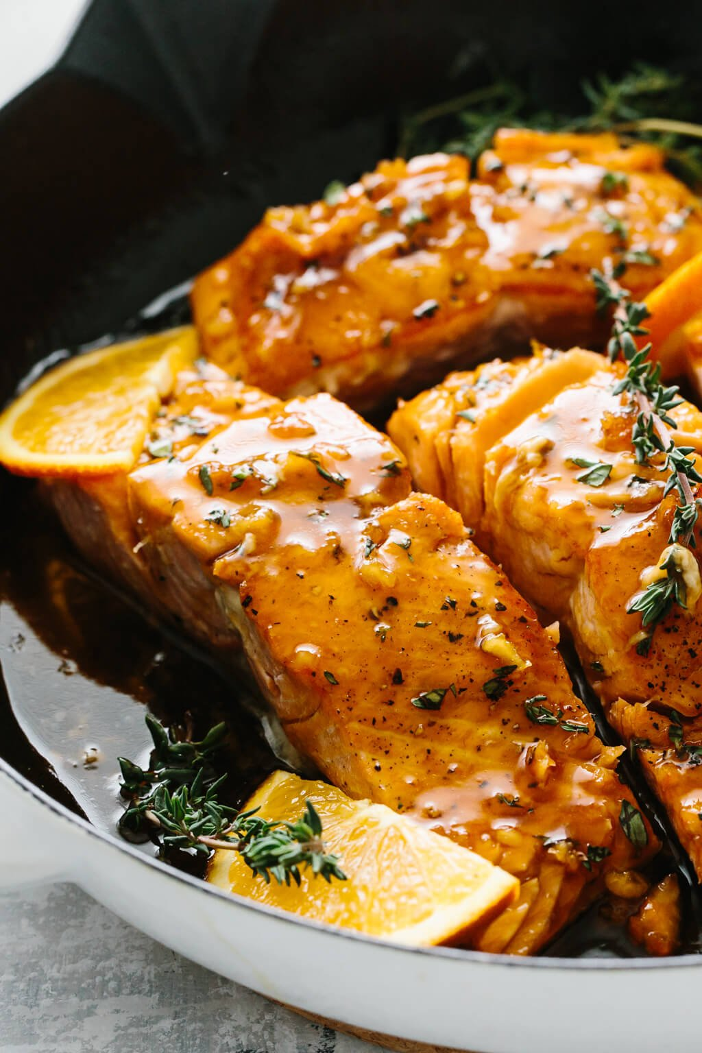 Four salmon filets in a pan with orange slices and thyme on top.