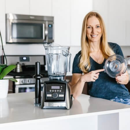 Girl standing next to Vitamix Blender pointing to the lid.
