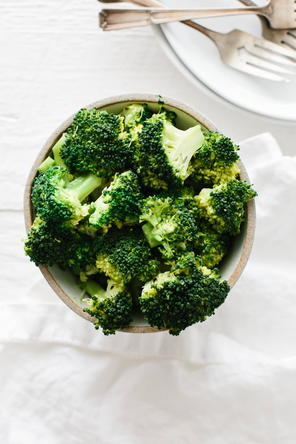 Top down view of steamed broccoli in a grey bowl on a white background.
