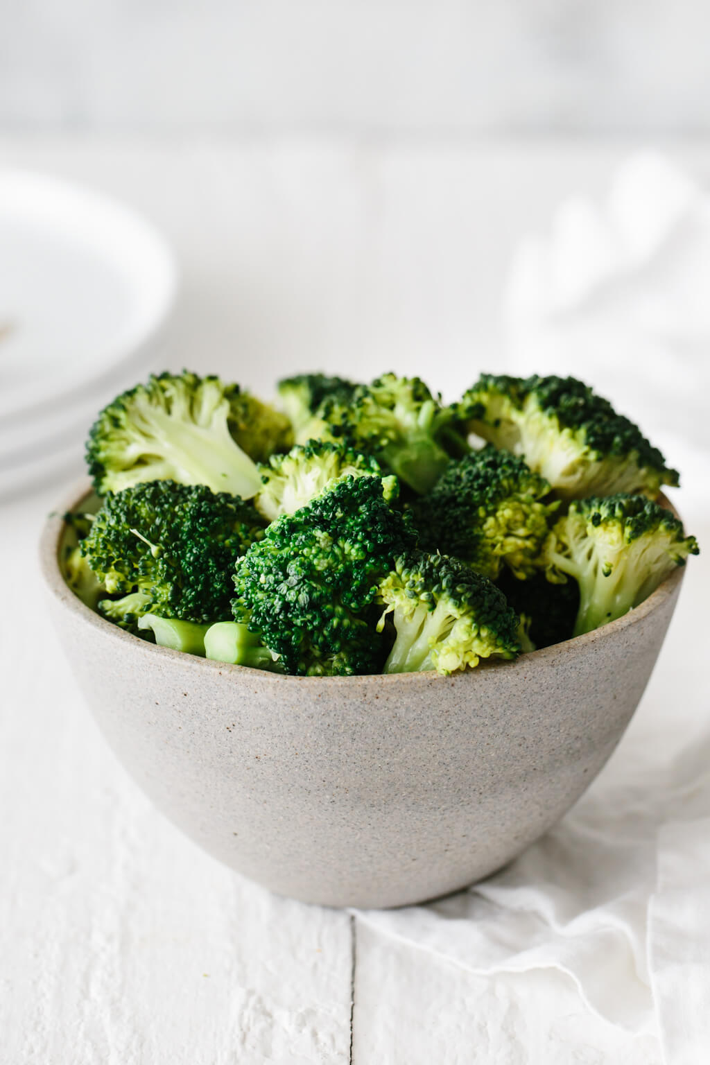 Steamed broccoli in a grey bowl on a white background.