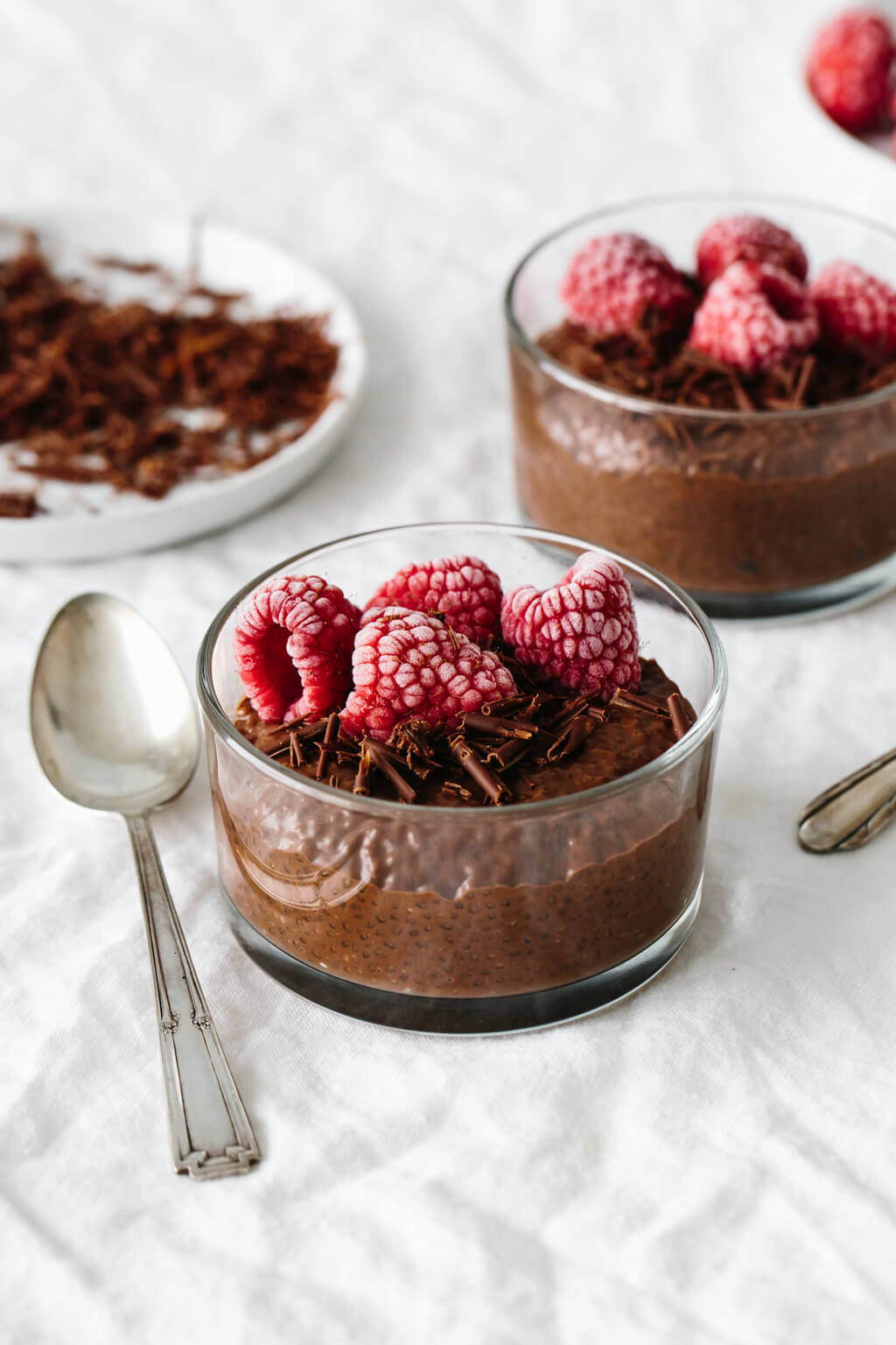Chocolate chia pudding in a dessert glass with frozen, frosted raspberries on top.