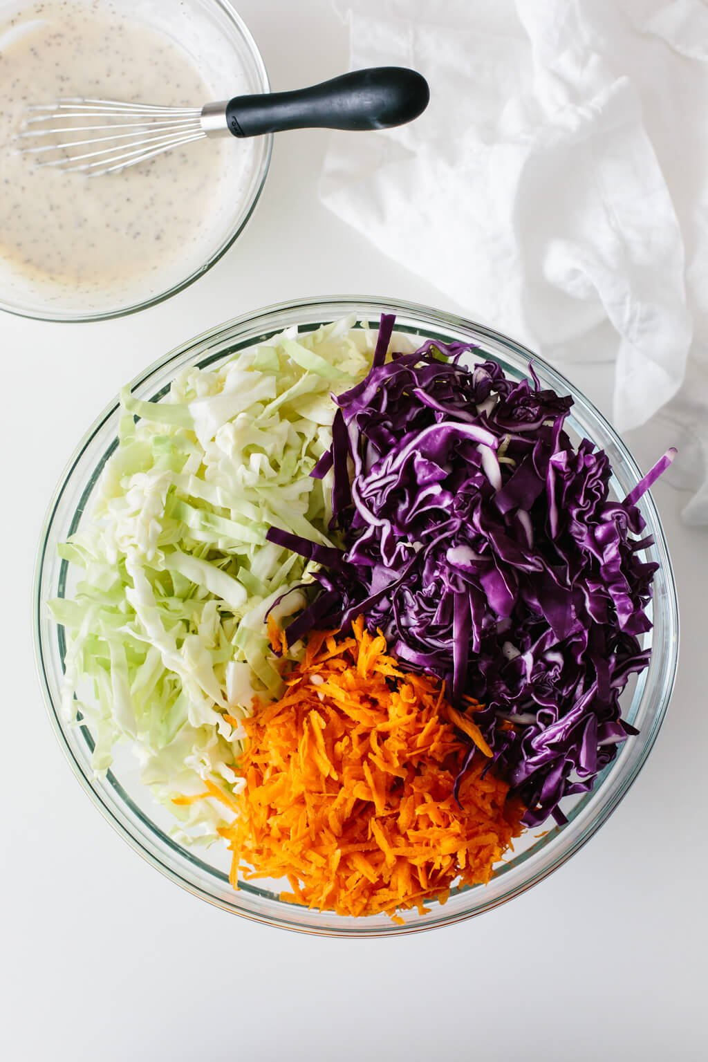 Coleslaw ingredients in a mixing bowl with coleslaw dressing on the side.