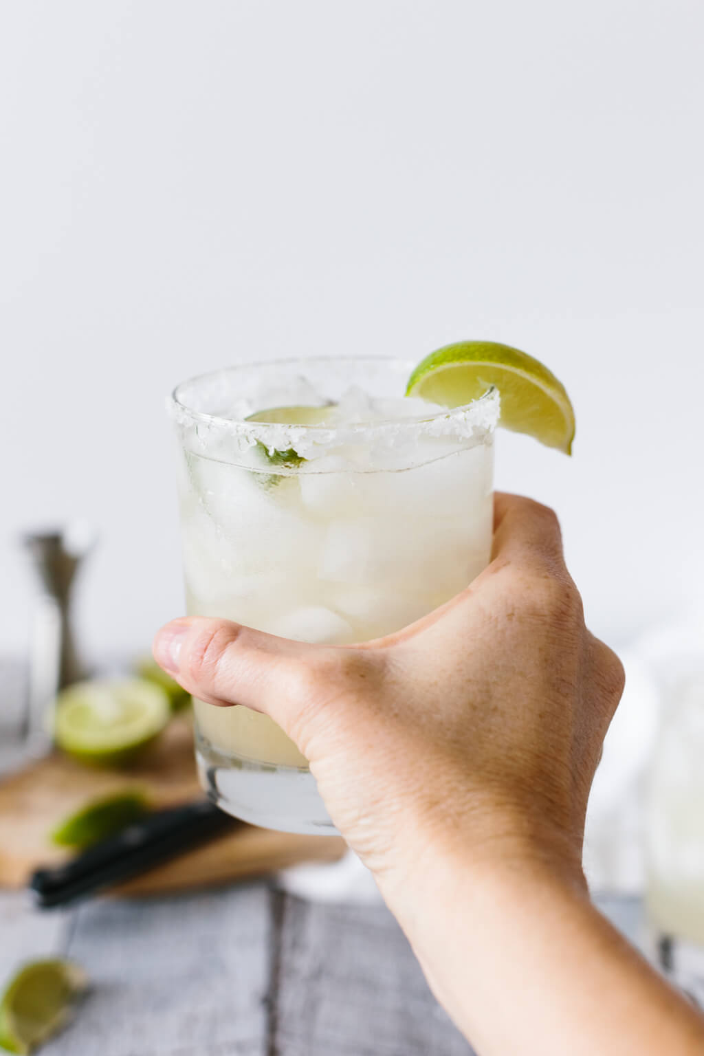Holding a margarita in a glass with a lime wedge.
