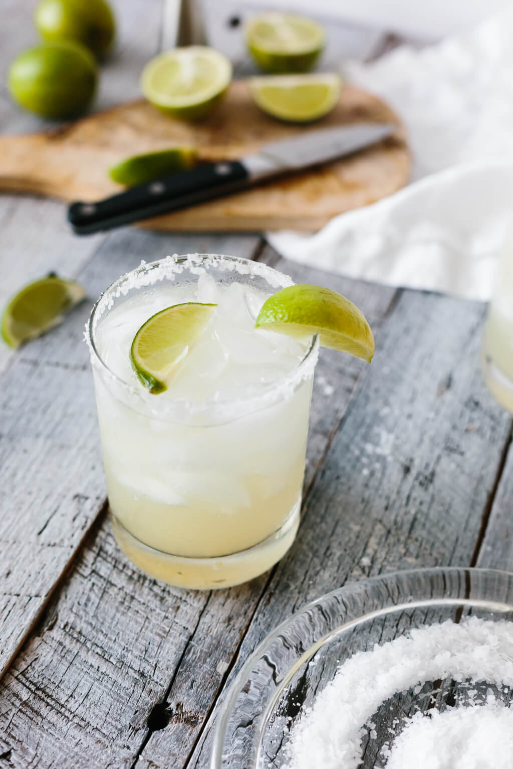 Margarita in a glass with lime wedges.