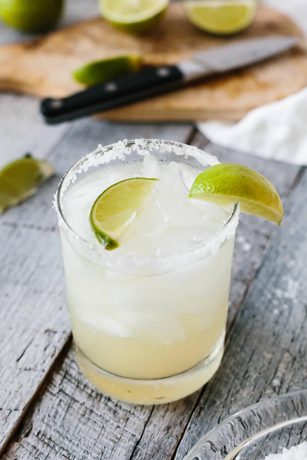Margarita in a glass with limes on top and in the background.