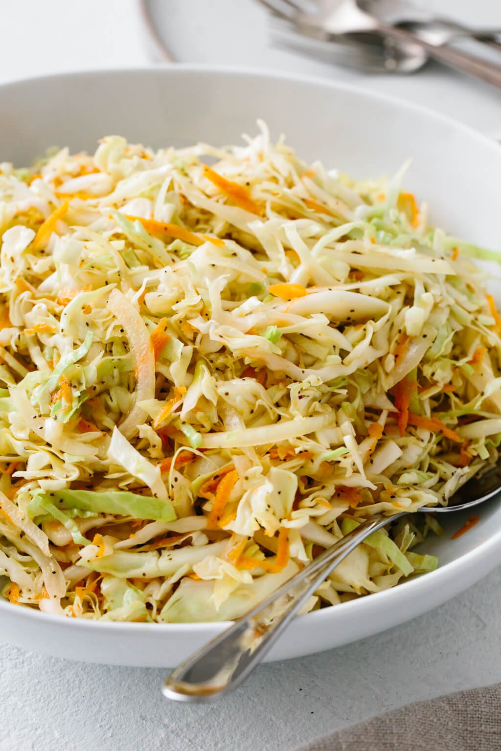 Vinegar coleslaw in a white bowl.