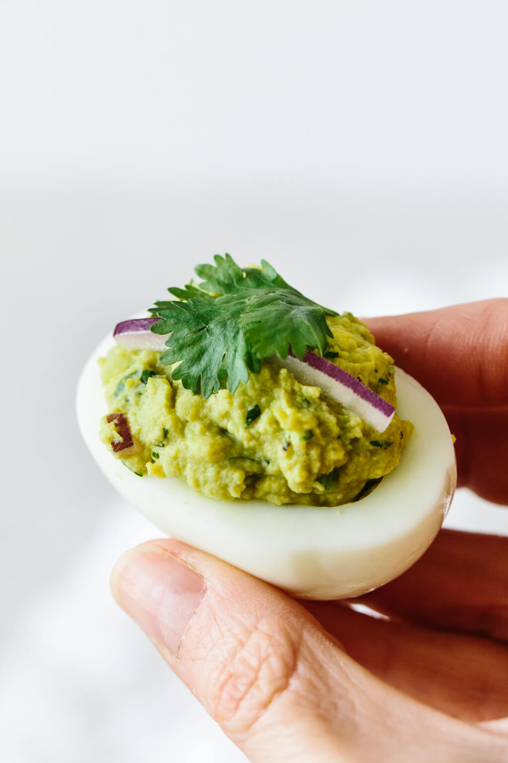 Close up photo of hand holding avocado deviled eggs.
