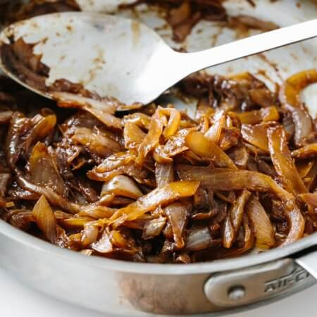Caramelized onions in a stainless steel pan.