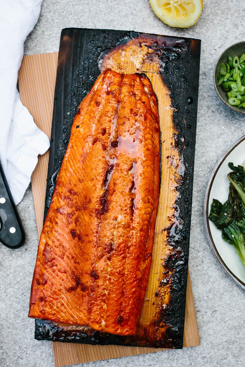 Cedar plank salmon on charred grilling plank next to plate of bok choy.