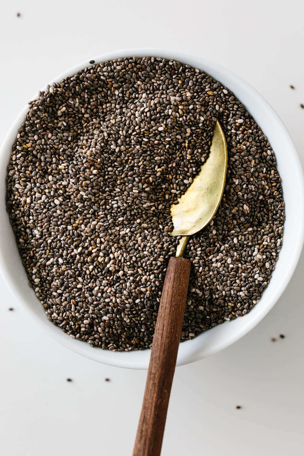 Chia seeds in white bowl with gold spoon.