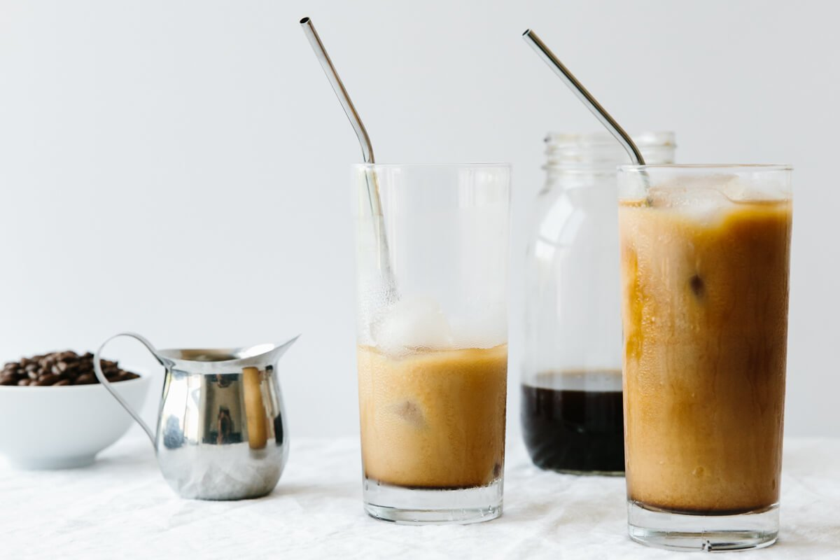 Cold brew coffee in several glasses next to creamer and coffee beans.