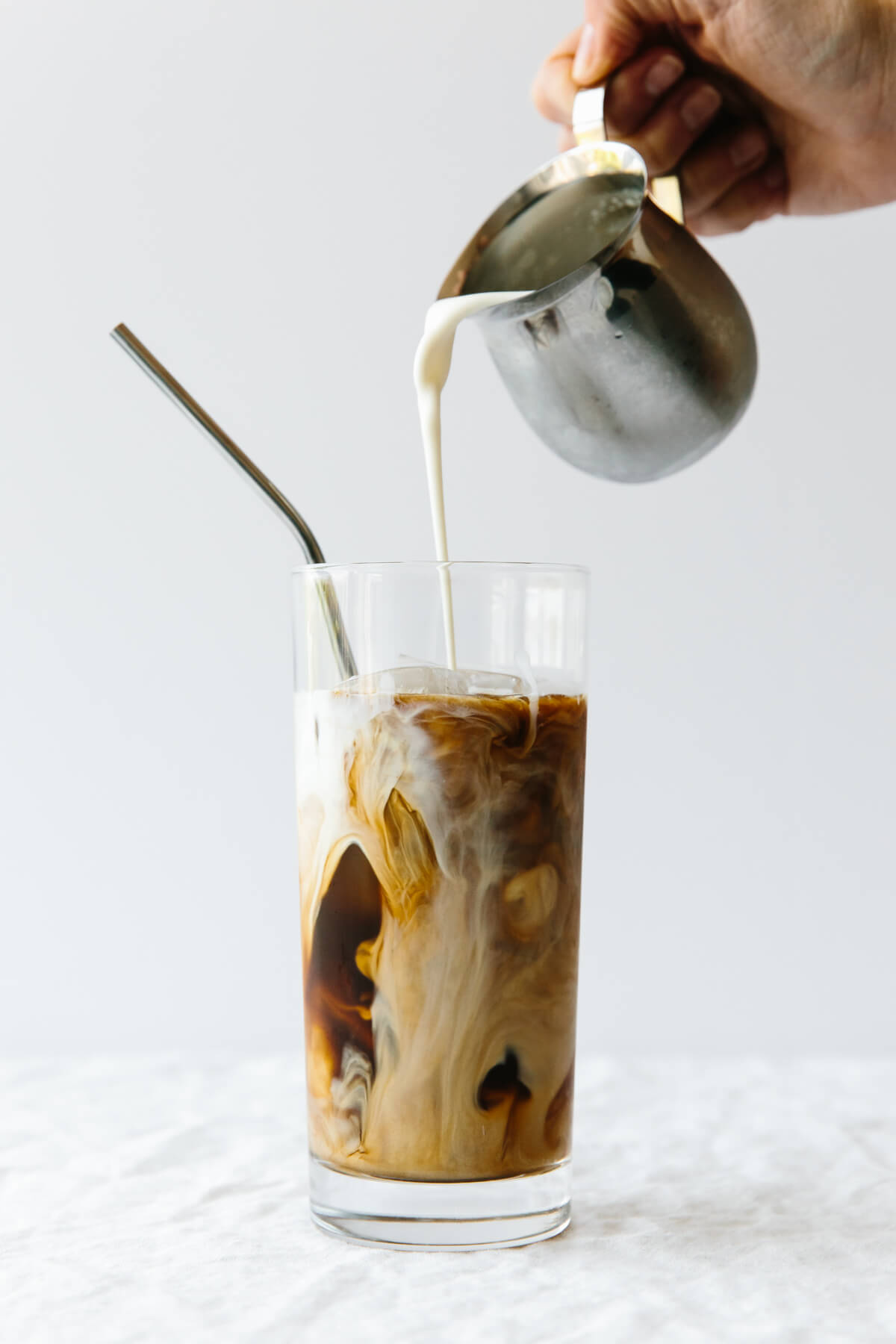 Pouring creamer into a glass of cold brew coffee.