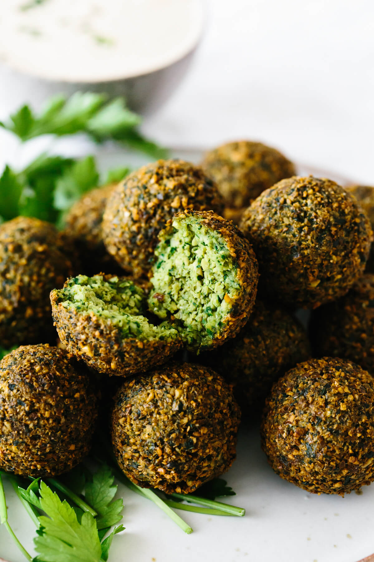 A plate of falafel with one cut open in half.