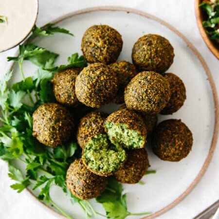 Several falafel on a serving plate.