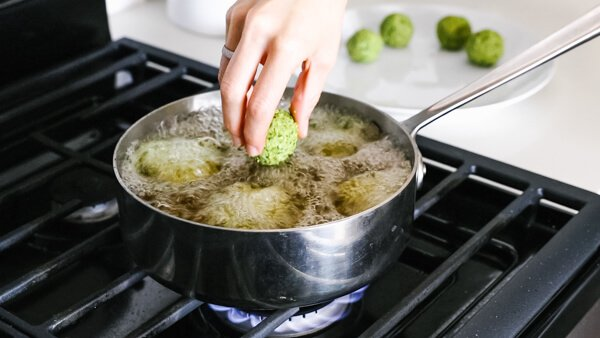 Cooking the falafel in a pan of oil on the stove.