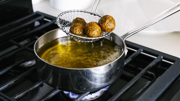Removing the falafel from the pan once they're cooked and golden.