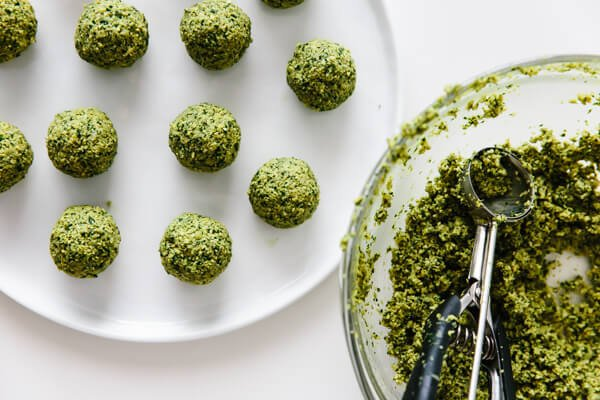 Scooping balls of falafel from the raw mixture.