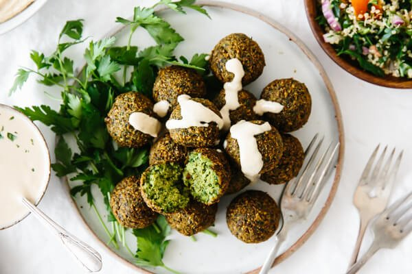 A plate of falafel drizzled with tahini sauce.