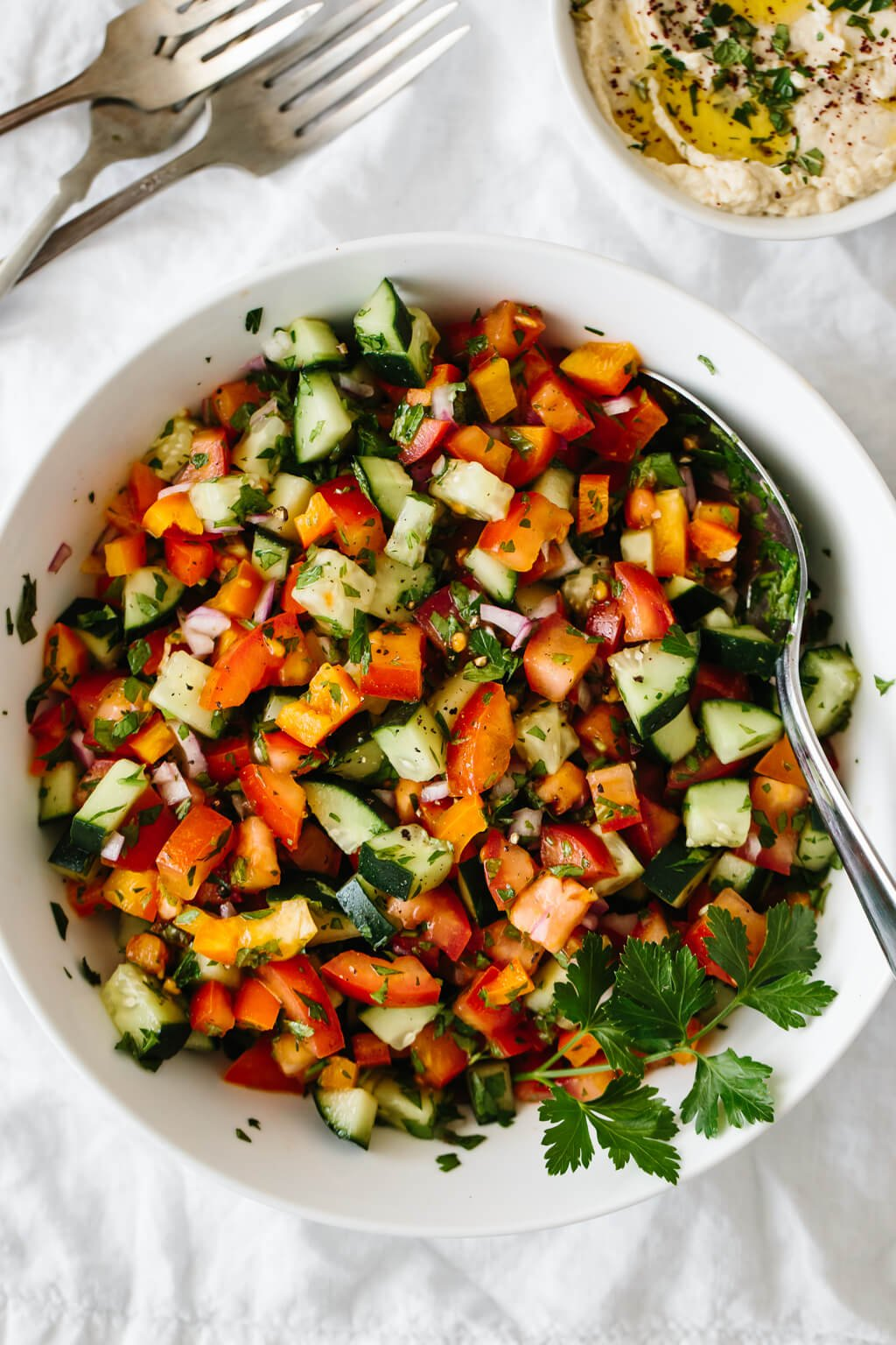 Israeli salad made from tomatoes, cucumber, bell pepper, red onion and herbs in a white bowl.