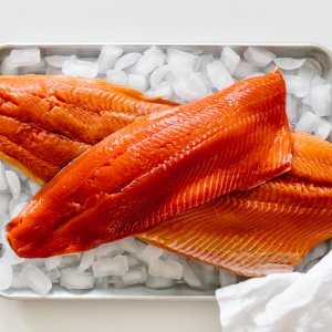 Raw salmon filets on a tray of ice.