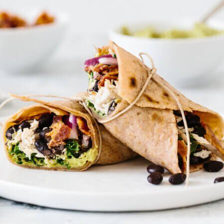 Healthy chicken wrap cut in half on a white plate.