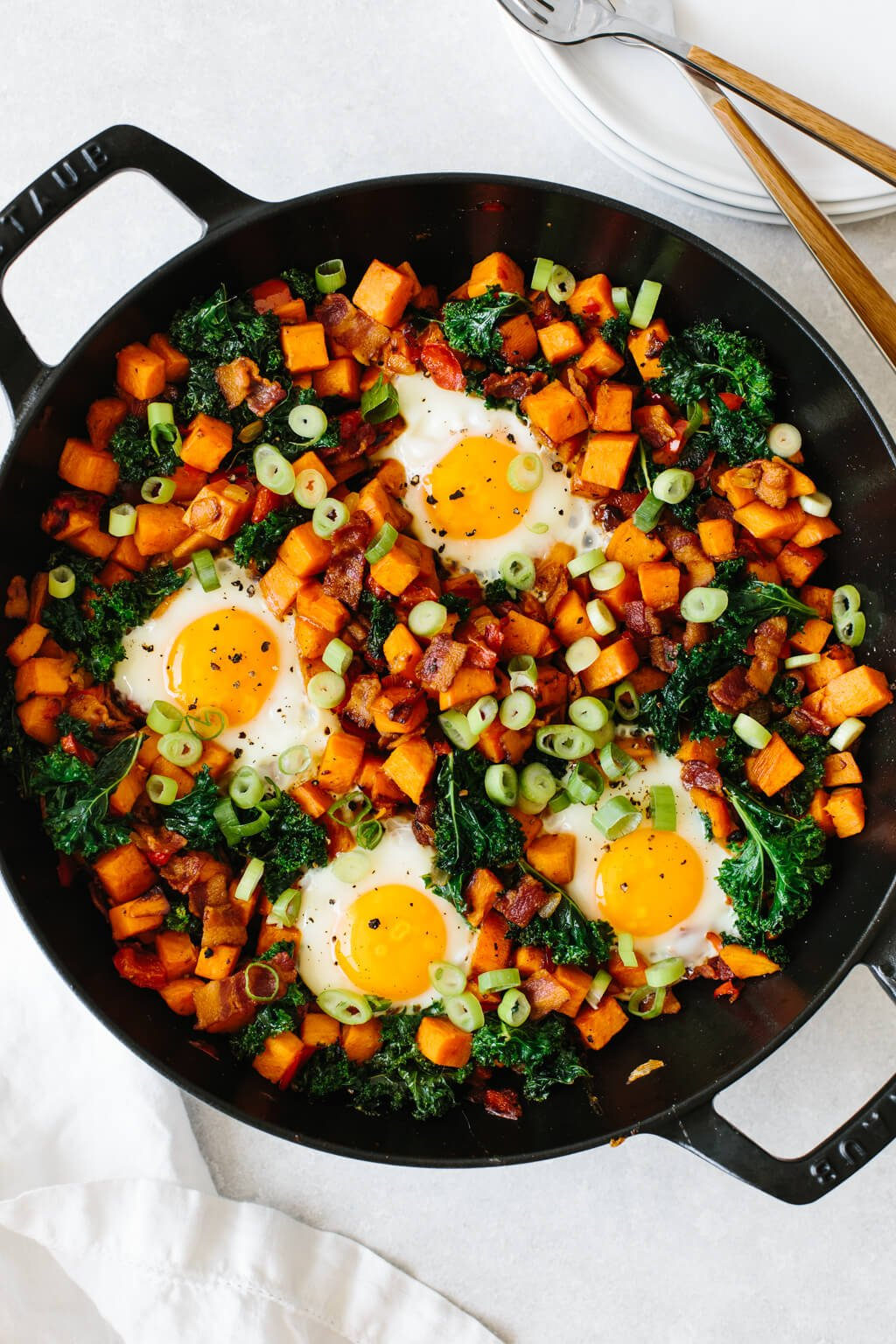 Cubed sweet potato and vegetables in a skillet with eggs.