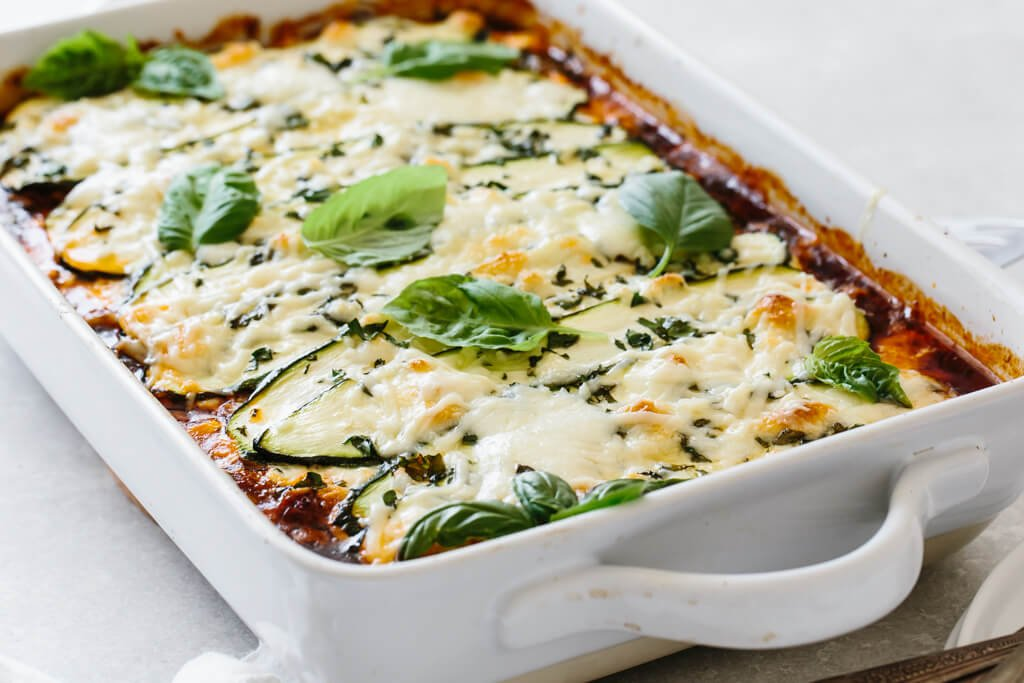 Zucchini lasagna in a white casserole pan.