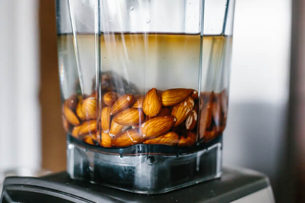 Almonds in a blender with water and other ingredients.