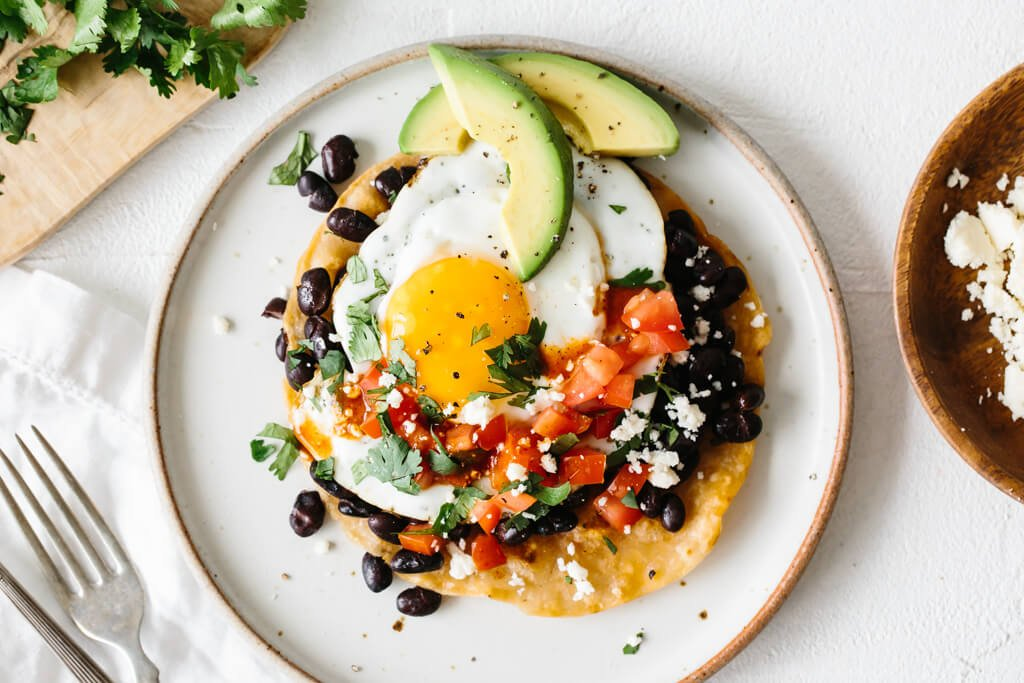 Huevos rancheros on a white plate next to cilantro and cotija cheese.