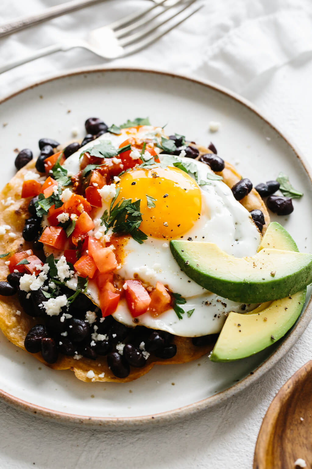 Huevos rancheros on a white plate next to forks.