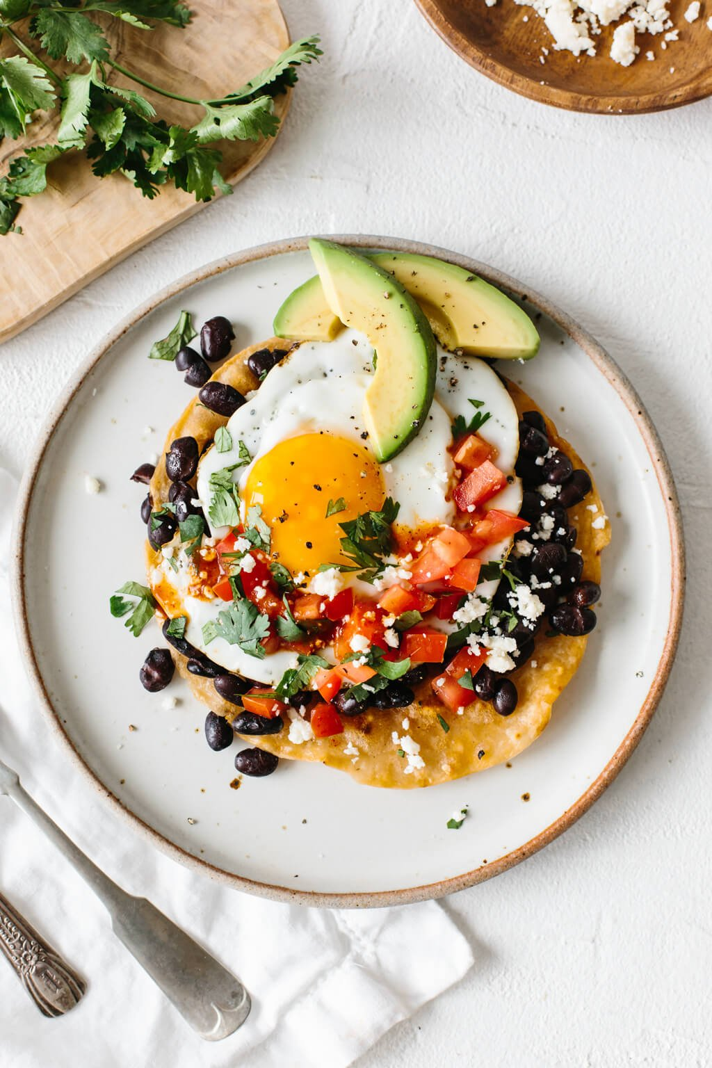 Huevos rancheros on a white plate topped with slices of avocado.