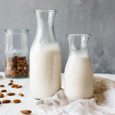 Homemade almond milk in glass containers.