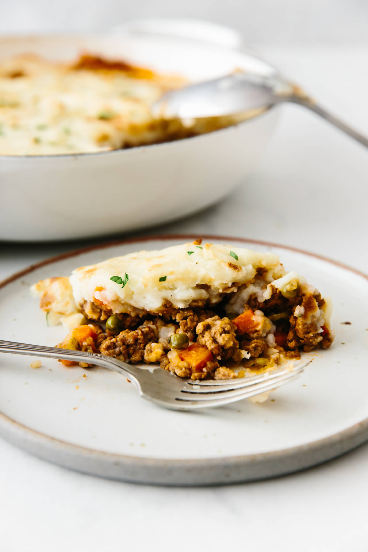 An individual serving of Shepherd's pie on a plate.