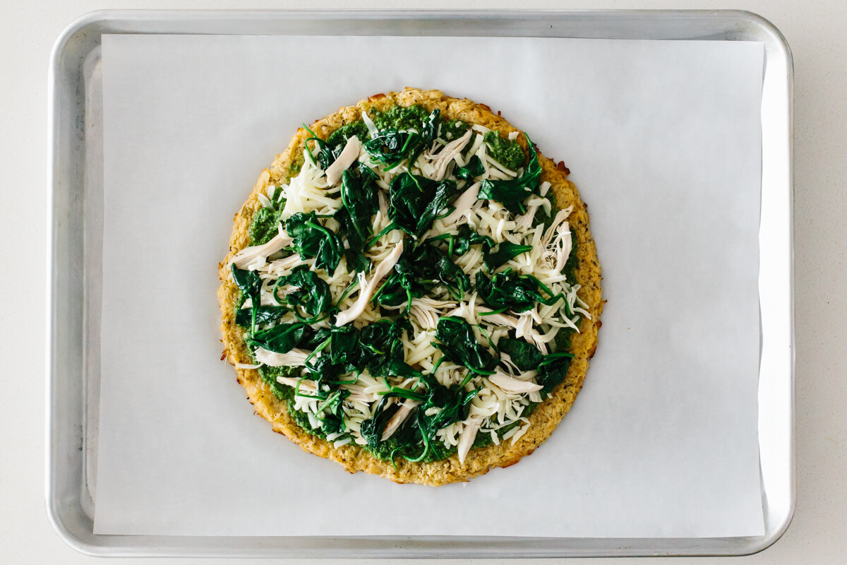 Making cauliflower pizza crust with toppings.