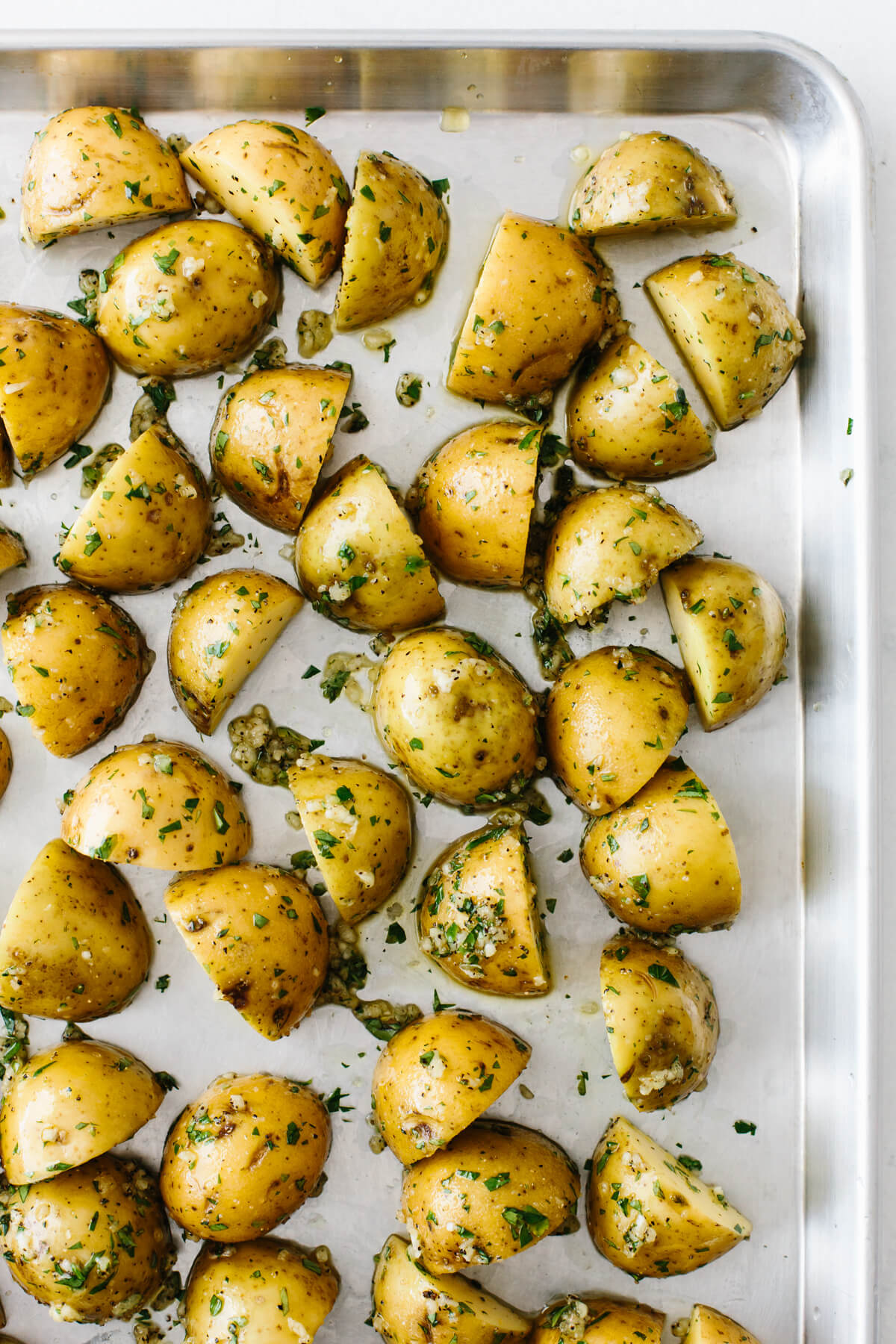 Potatoes on a baking sheet to get roasted in the oven.