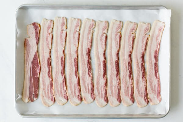 Raw bacon on a parchment lined baking tray.