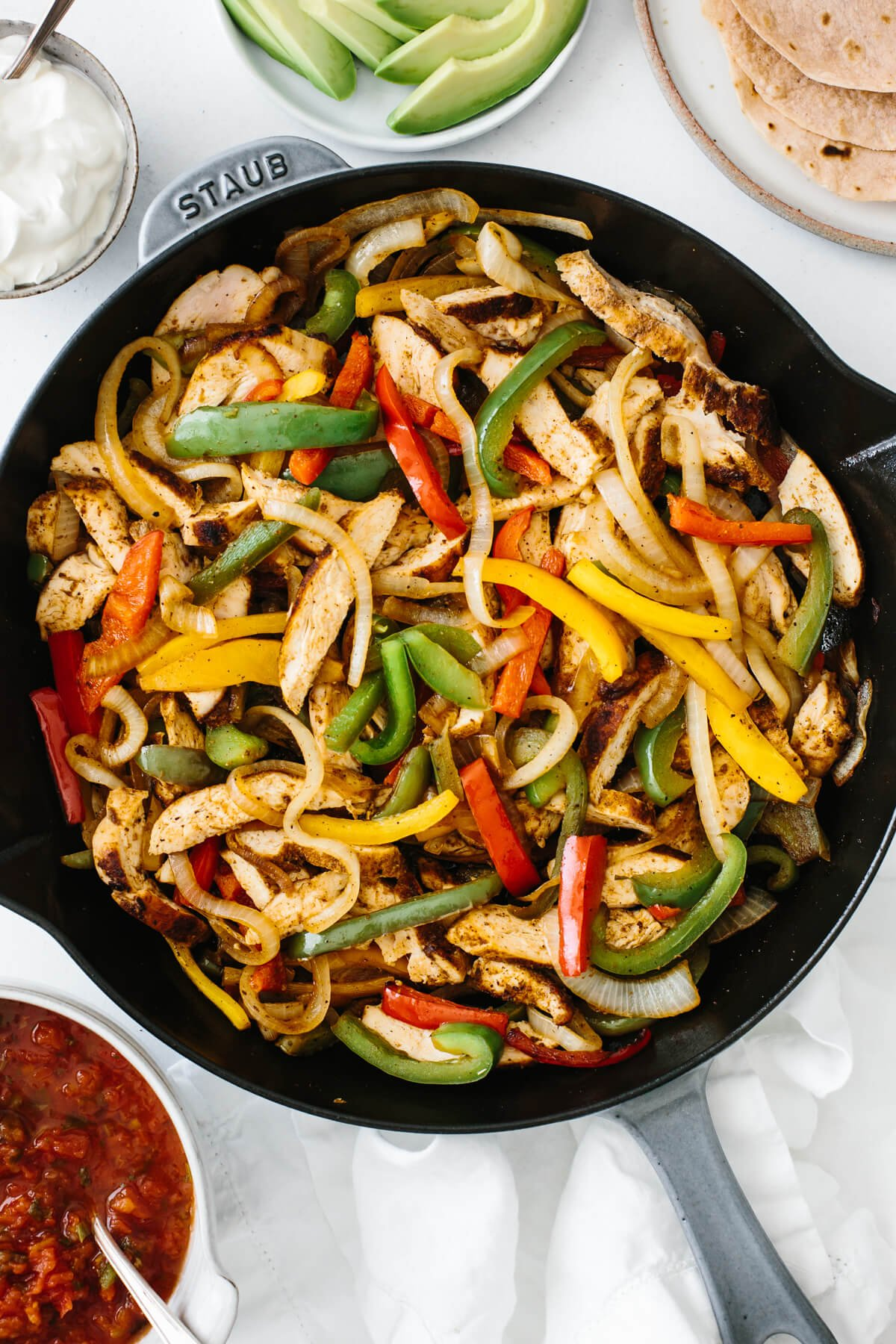 Chicken fajitas in a pan on a table with toppings.