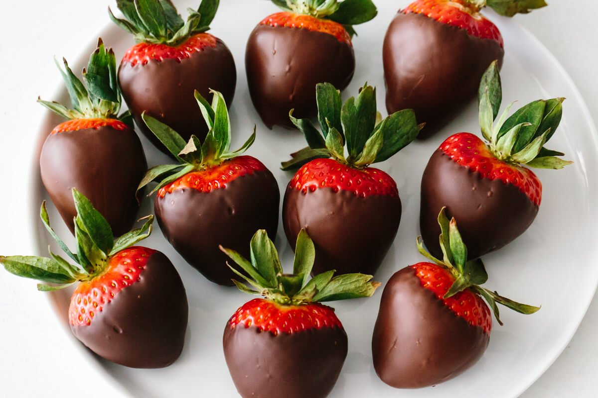 Several chocolate covered strawberries on a plate.