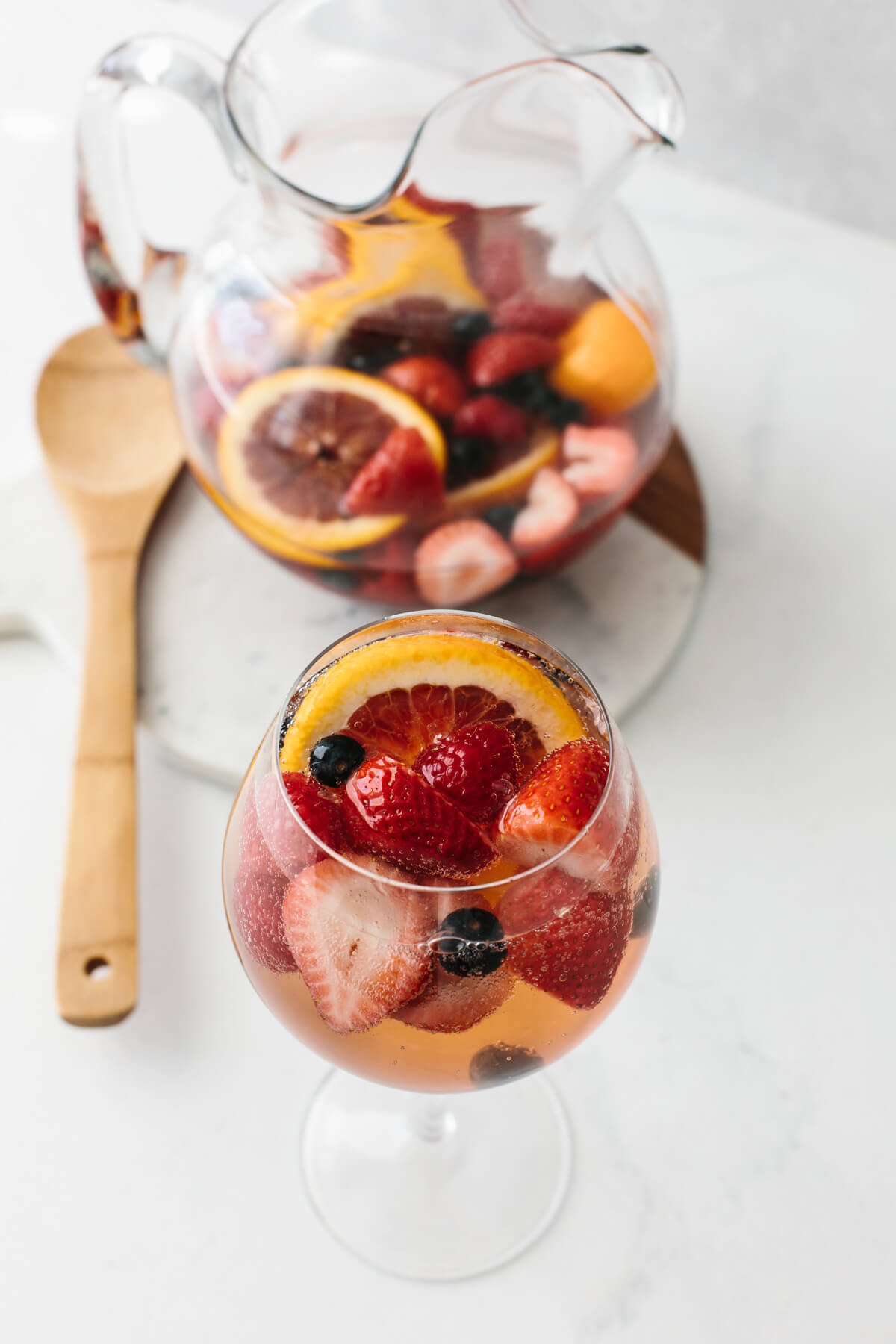 Moscato sangria in a glass next to pitcher.