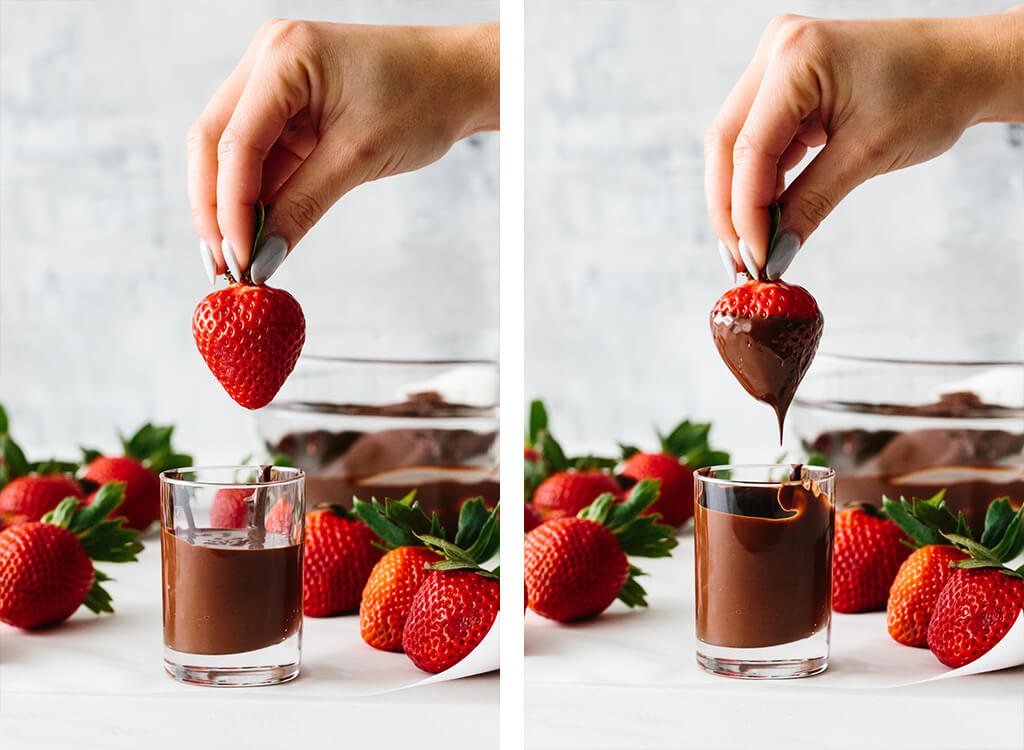 Dipping a strawberry in melted chocolate.