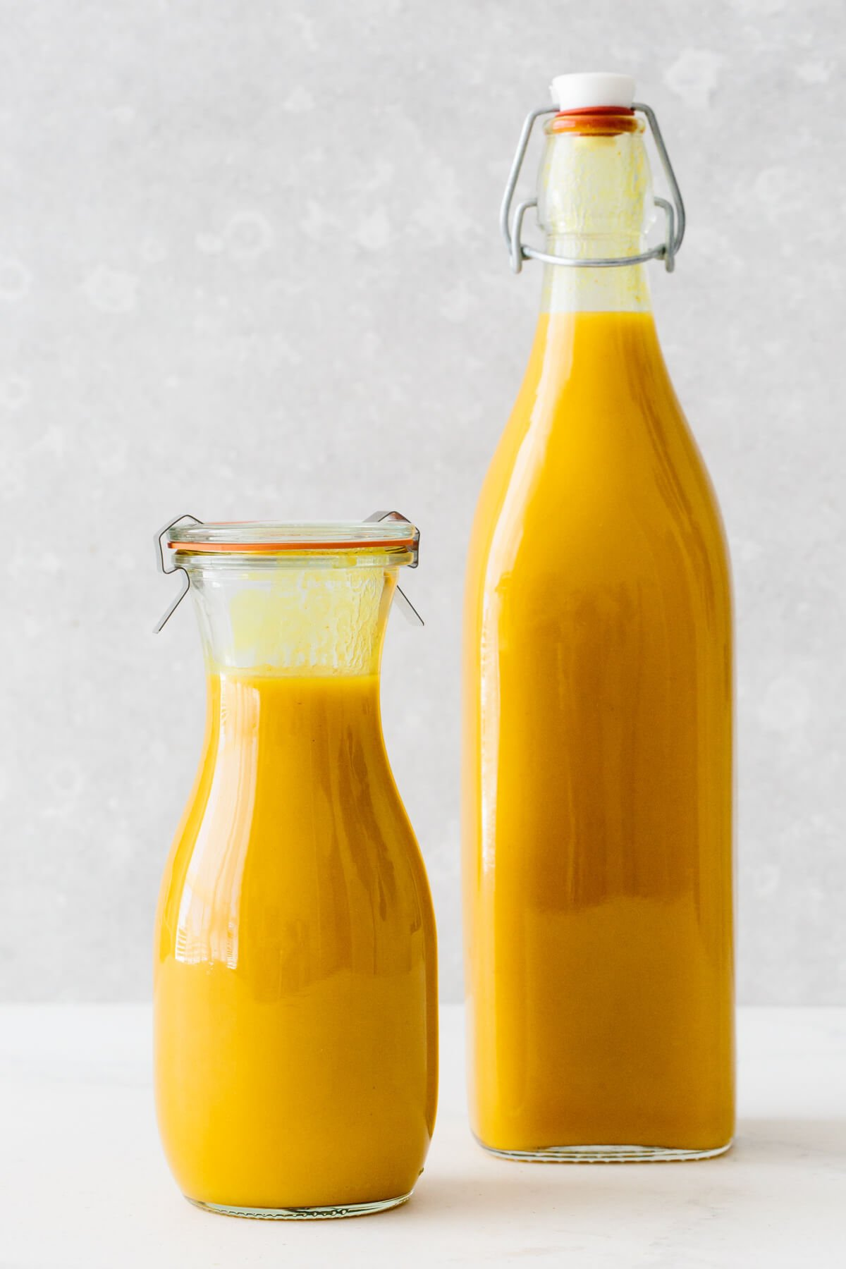 Jamu juice in two glass storage containers.