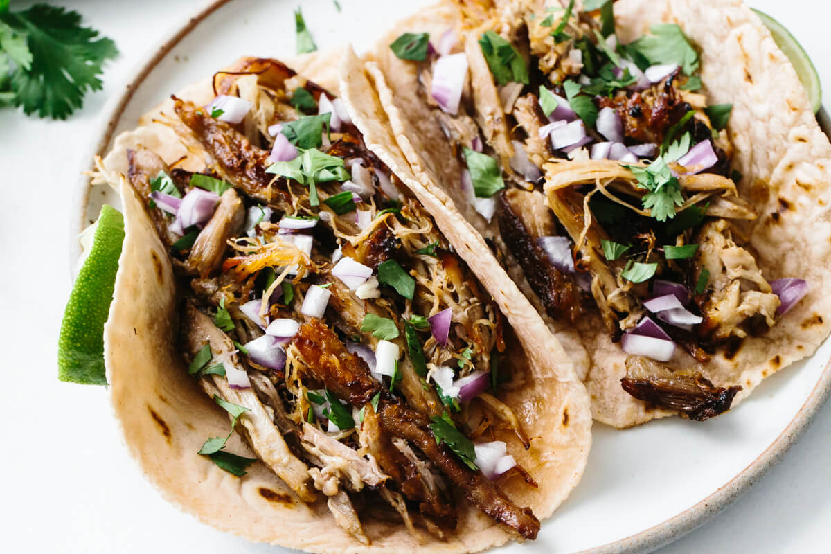 Two carnitas tacos on a plate with toppings.