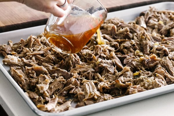 Pouring liquid on top of shredded carnitas on a sheet pan.