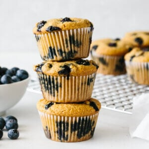 Paleo blueberry muffins stacked on top of each other.