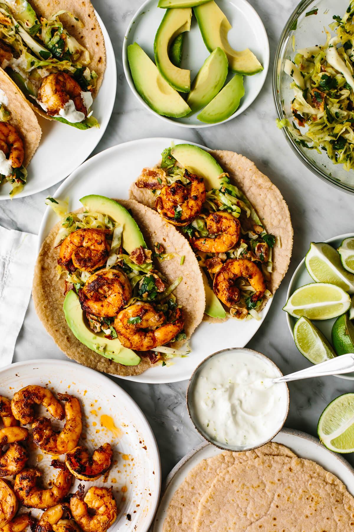 Shrimp tacos in the center of a table next to tortillas, avocado, and lime crema.