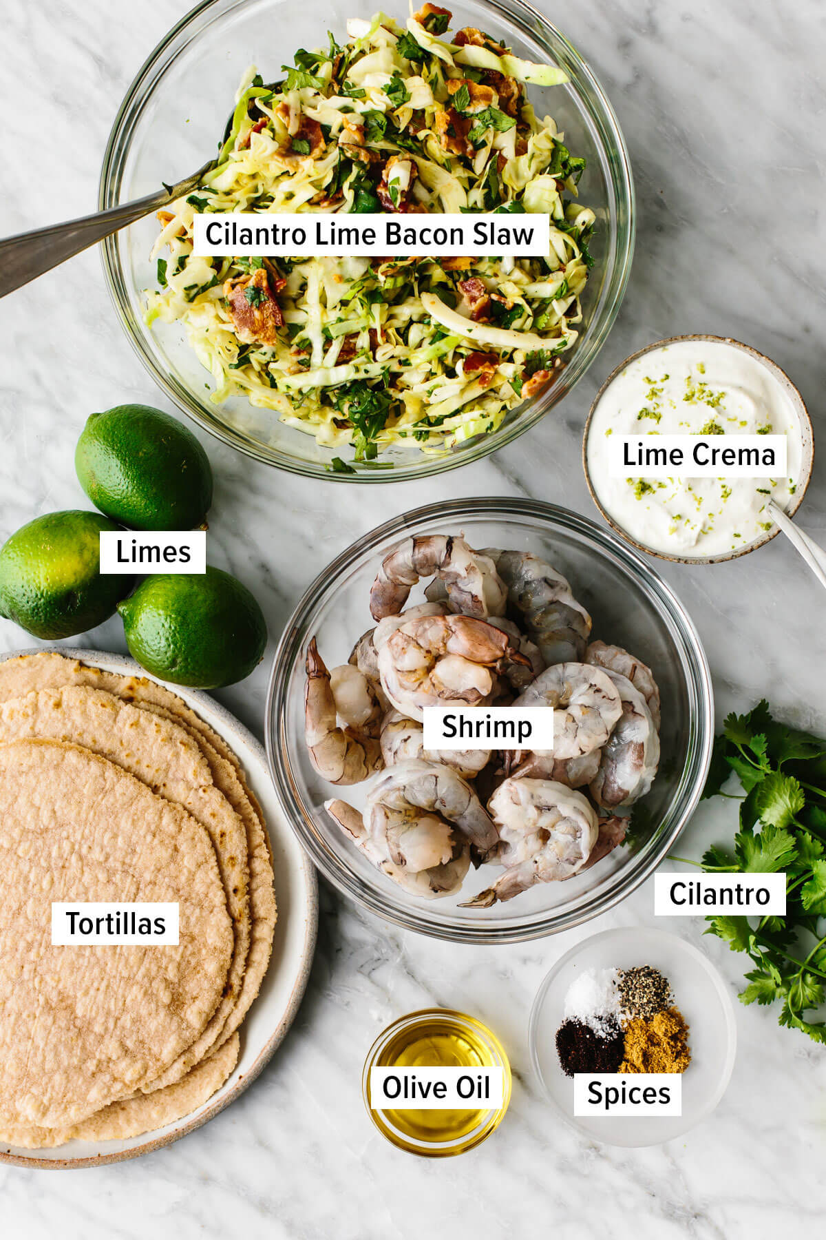 Ingredients for shrimp tacos with cilantro lime slaw on a table